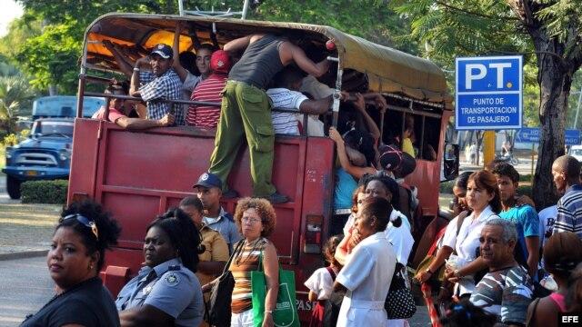 Varias personas suben a un camión de transporte de pasajeros en Santiago de Cuba.