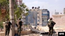 Fotografía distribuida por la agencia oficial siria de noticias SANA que muestra a soldados sirios durante enfrentamientos con rebeldes en las calles de Alepo, Siria.