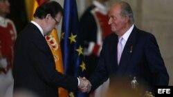 El Rey Juan Carlos estrecha la mano del presidente del Gobierno, Mariano Rajoy, tras firmar su abdicación.
