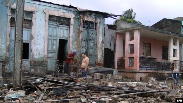 """Dos hombres limpian escombros en una casa que ha sido parcialmente destruida por el paso del huracán """"Sandy"""", en la ciudad de Guantánamo (Cuba)."""