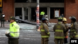 Bomberos y policías acuden a uno de los lugares de Bogotá donde estallaron el jueves sendos artefactos explosivos. Al menos ocho personas resultaron heridas.