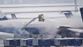 Personal limpia la nieve sobre un avión de United Airlines
