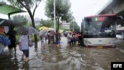 Varias personas tratan de subir a un autobus en una carretera inundada en Tianjín, al norte de China, hoy jueves 26 de julio de 2012. La reciente oleada de aguaceros han matada a más de 100 personas en China. EFE/Geno Zhou PROHIBIDO SU USO EN CHINA