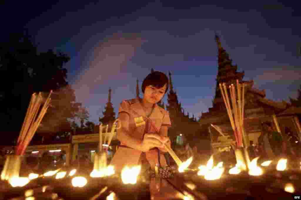 Una fiel enciende una vela durante la primera noche del Año Nuevo en la padoga dorada de Shwedagon en Rangún, Birmania.