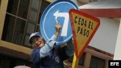 Un hombre instala una señal de tránsito en una calle de la Ciudad de Holguín, Cuba.