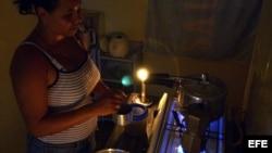 Una mujer prepara unos platos de comida en la cocina, iluminada con velas, durante un apagón en el barrio de Alamar.