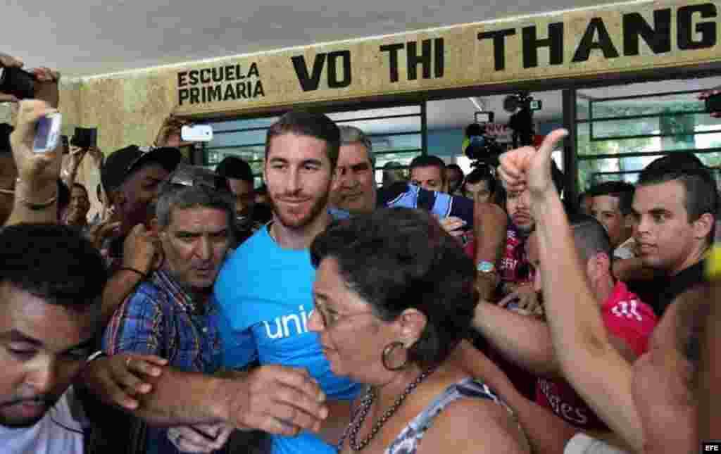 Aficionados al fútbol persiguieron al defensa madridista Sergio Ramos y lo recibieron con aplausos y gritos en la visita que cursó a una escuela habanera.