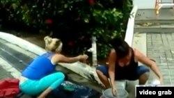 Lisandra Faray, (izq) opositora cubana, toma agua de un grifo junto a la calle para lavar la ropa. Faray y otros 15 cubanos están plantados hace seis semanas ante la sede de la ACNUR en Trinidad -Tobago (America Teve)