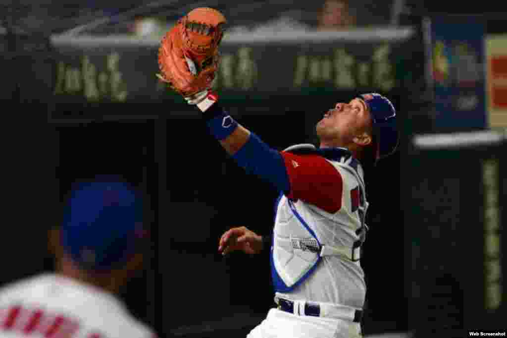 El receptor cubano Frank Morejón intenta capturar un batazo foul.