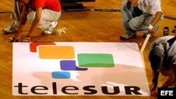 """Trabajadores dan los últimos detalles a un cartel publicitario del canal latinoamericano de televisión """"Telesur""""."""