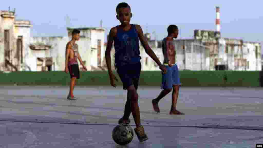 Jóvenes cubanos juegan fútbol donde encuentran espacio sin importar la escasez de zapatos o balones.