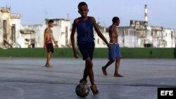Niños jugando al fútbol en calles y plazas cubanas.