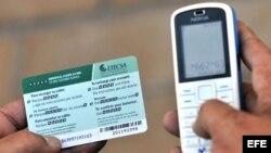 Un hombre recarga un teléfono celular con una tarjeta prepago de la empresa de Telecomunicaciones de Cuba (ETECSA), en La Habana.