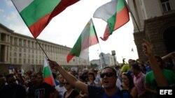 Un grupo de manifestantes ondean banderas de Bulgaria durante una protesta anti-gobierno en Sofía (Bulgaria).