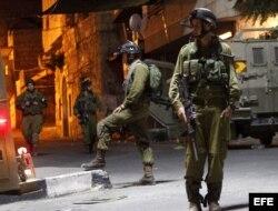 Soldados israelíes patrullan las calles de Hebrón, cerca de donde fueron encontrados los cadáveres de tres adolescentes judíos.