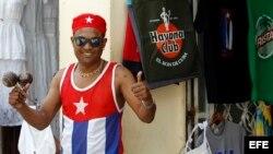 Un joven vestido con los colores de la bandera cubana posa para una foto en una calle de La Habana.