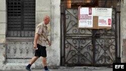 Foto Archivo. un hombre cerca de un cartel que anuncia elecciones municipales en Cuba.
