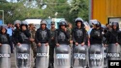 Miembros de la policía impiden el paso de migrantes cubanos hacia Nicaragua en el puesto fronterizo de Peñas Blancas (16 de noviembre, 2015). EFE