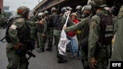 Militares retiran a una mujer que bloqueaba el paso de una tanqueta de la Guardia Nacional durante una manifestación.
