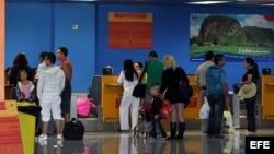 Varias personas chequean sus documentos para abordar un vuelo hacia Miami (EEUIU), en la Terminal 2 del aeropuerto José Martí de La Habana (Cuba).