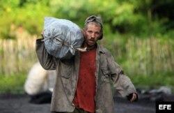 Un campesino cubano carga un saco de carbón.