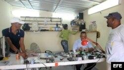 Un hombre arregla un celular en su negocio de reparación hoy, viernes 19 de diciembre de 2014, en La Habana (Cuba).