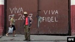 Unas personas caminan frente a un mensaje alusivo al líder cubano Fidel Castro, en un barrio de La Habana (Cuba).