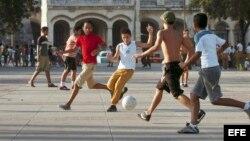 Varios estudiantes cubanos juegan fútbol en un parque en La Habana, Cuba.