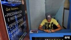Un cuentapropista técnico en reparación de celulares espera llegada de clientes en La Habana.