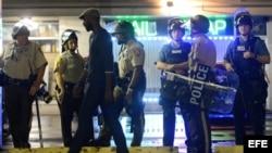 Policías y manifestantes en Ferguson, Misuri, tras el toque de queda.