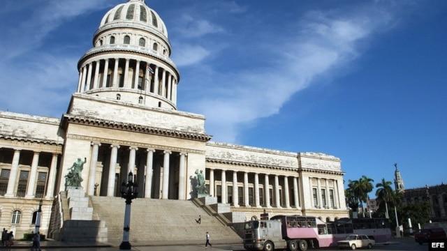 """Un """"camello"""" (autobús público) pasa frente al Capitolio Nacional, sede del ministerio de Ciencia."""