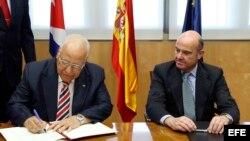 El ministro español de Economía y Competitividad en funciones, Luis de Guindos (d), y el vicepresidente del Consejo de Ministros de Cuba, Ricardo Cabrisas Ruiz (i), durante la firma de los acuerdos para reestructurar la deuda cubana con España a medio y l