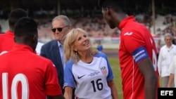 Jill Biden, y el Embajador de EEUU en Cuba, Jeffrey De Laurentis, saludan a los futbolistas cubanos en el estadio Pedro Marrero de La Habana.