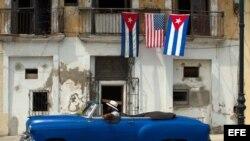 Un automóvil antiguo pasa junto a una casa que exhibe las banderas de Estados Unidos y Cuba en una calle de La Habana (Cuba).