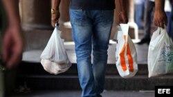 """Varias personas caminan llevando bolsas plásticas, conocidas en Cuba como """"jabitas""""."""