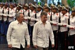 Raúl Castro (i) y el presidente de Colombia, Juan Manuel Santos (d), pasan revista a las tropas formadas para la ceremonia oficial de recibimiento 17 de julio de 2017.