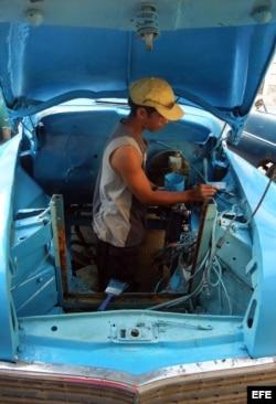 Un hombre pinta el interior de la carrocería de un viejo auto de fabricación norteamericana.