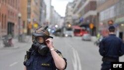 Miembros de la policía sueca se ajustan las máscaras antigas en la zona donde un camión que ha atropellado a varias personas y se ha estrellado contra una tienda de la calle comercial de Drottninggatan en el centro de Estocolmo, Suecia hoy 7 de abril de 2