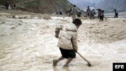 Fotografía de archivo fechada el 30 de abril de 2012 que muestra a varias personas intentando limpiar de barro una carretera tras una lluvia torrencial seguida de un corrimiento de tierra en la provincia de Badakhshan, en Afganistán.