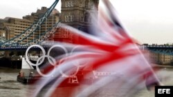 Una embarcación navega por el rio Támesis con los aros olímpicos.