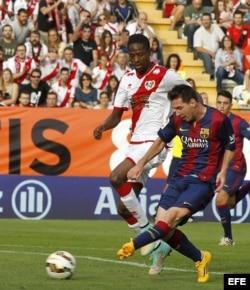 El delantero argentino del Barcelona Leo Messi (d) supera al defensa senegalés del Rayo Vallecano Abdoulaye Ba.