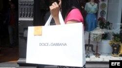 Una clienta pasa con una bolsa de la firma de moda Dolce & Gabbana.