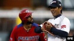 El puertorriqueño Angel Pagan (izda) conversa con el japonés Atsunori Inaba durante el partido que les enfrentó a Puerto Rico en el Clásico Mundial de Béisbol 2013