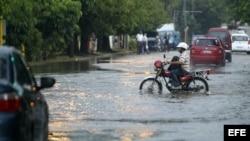 Un hombre conduce una motocicleta por una calle inundada el miércoles en La Habana.