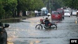 Un hombre conduce una motocicleta por una calle inundada el miércoles en La Habana