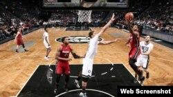 Brook López (c) intenta bloquear la anotación del jugador del Miami Heat.