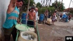 """ARCHIVO. Varias personas con cubos y tanques hacen cola en un """"Punto de agua""""."""