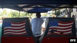 Un hombre espera montado en su bicitaxi con banderas de Estados Unidos pintadas al fondo.