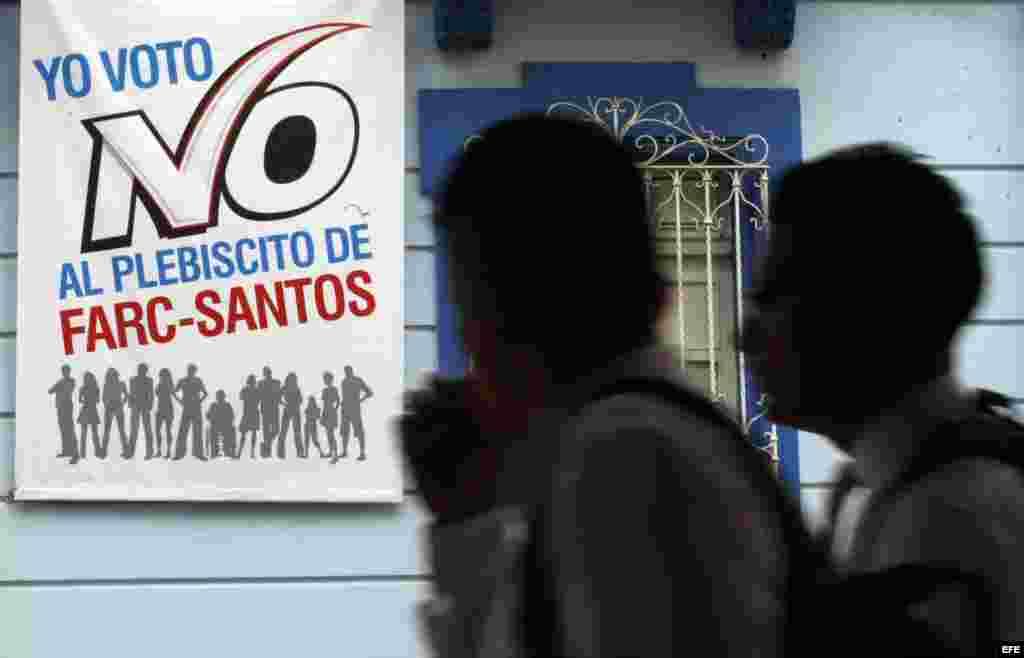 Un grupo de personas pasa junto a una pancarta que promueve el voto por el No en el plebiscito hoy, viernes 30 de septiembre de 2016, en Cali (Colombia). El plebiscito que el domingo debe ratificar o no los acuerdos de La Habana, ha generado cientos de im