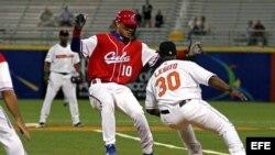 Foto archivo. El holandés Rily Legito (d) saca out al cubano Yuliesky Gourriel de Cuba durante el cuarto juego del Clásico Mundial de Béisbol disputado el 9 de marzo de 2006, en el estadio Hiram Bithorn de San Juan (Puerto Rico).